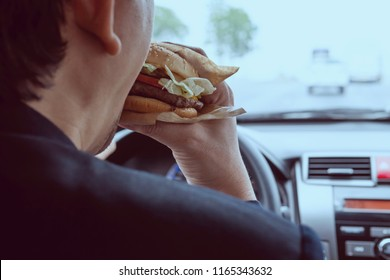 Man driving car while eating hamburger