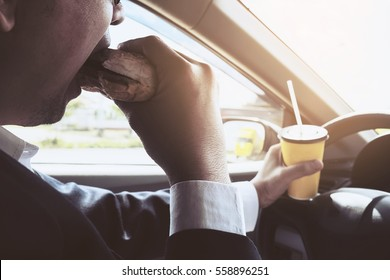 Man driving car while holding a cup of cold coffee and eating hamburger