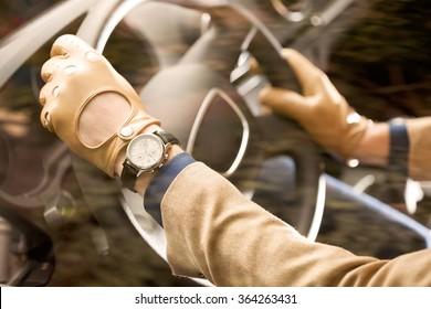man driving, detail shot, hands on the steering wheel, wearing leather men gloves