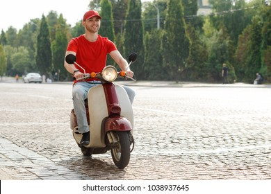 Man driving down a paved road on a motorcycle. Uplifted mood of a worker loving his job. Pizza delivery.