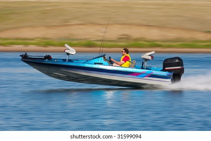 Man driving a fast boat with panned (motion blur) background.
