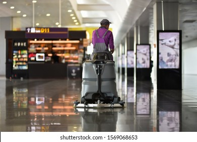 Man driving floor scrubber or floor cleaning device of cleaning service in airport