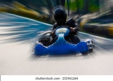 A man is driving Go-kart with speed in the park on karting track - front view.