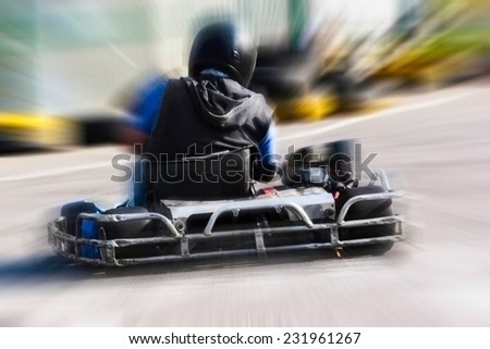 A man is driving Go-kart with speed in the park on karting track - behind view.