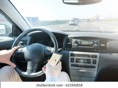 Man driving his car and following the phone gps direction, main focus is on the phone