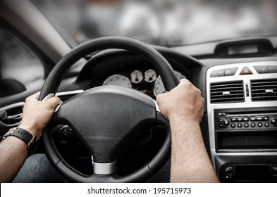 Man driving his car. Hands holding the wheel.