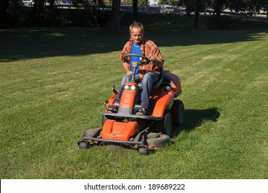 man driving a lawn mower in the city park
