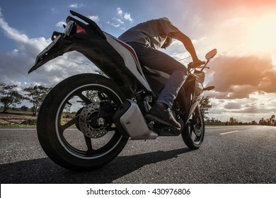 Man driving a motorcycle in backlit conditions.