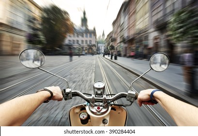 Man driving on scooter at old streets in city