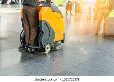 Man driving professional floor cleaning machine at airport or railway station.  Floor care and cleaning service agency
