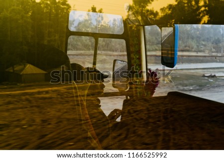 Man driving a public bus with blurry roads reflection in glass unique photo