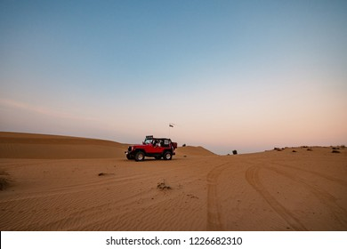 Man driving red jeep in the desert at dusk.