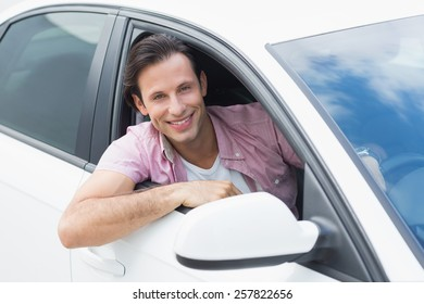 Man driving and smiling in his car