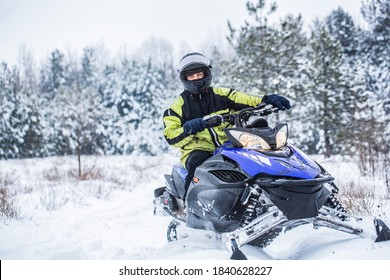 Man driving snowmobile in snowy forest. Man on snowmobile in winter mountain. Snowmobile driving.