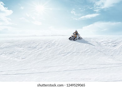 Man driving sports snowmobile in Finnish Lapland in a sunny day