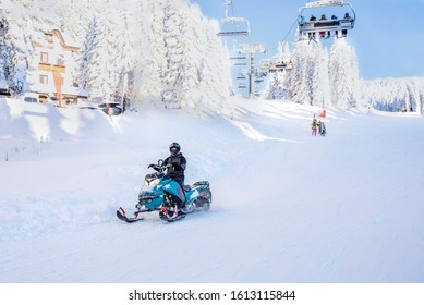 Man driving sports snowmobile in mountain ski resort