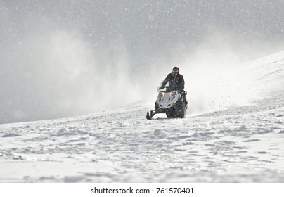 A man driving sports snowmobile in mountains