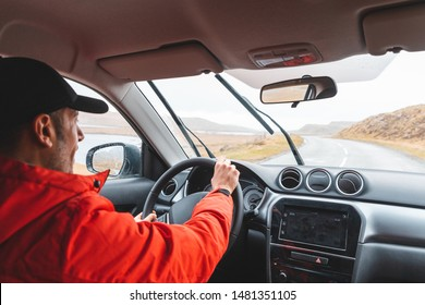Man driving SUV car on coastline road - Young man wearing red jacket driving on a rainy day in northern Europe alone a winding empty road - Travel and adventure
