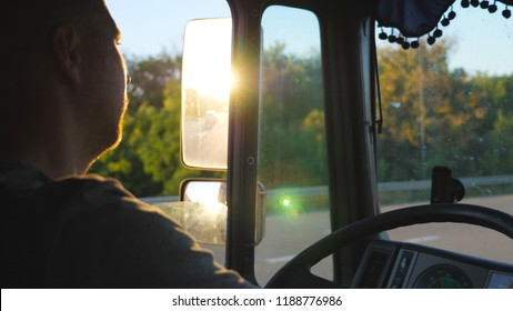 Man driving truck and carefully watching the road. Caucasian guy is riding through countryside with beautiful landscape at background. Profile of lorry driver inside the cab. Slow motion Close up.