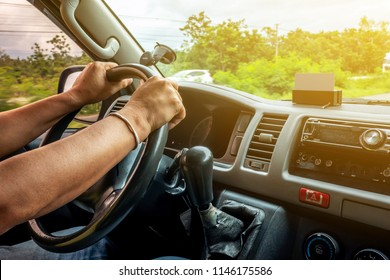 Man is driving vehicle while working or going to somewhere with flare from the outside in the sunny day.