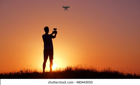 Man with drone on sunset