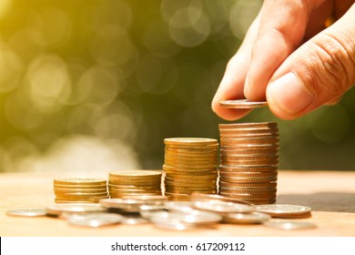 Man drop coin on coin bar show accumulation or savings of money.