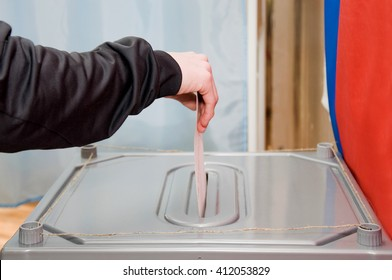 The man drops his ballot in the ballot box. Elections