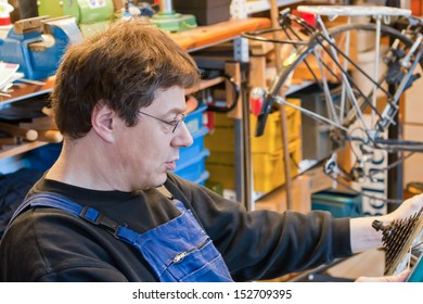 man in dungarees in his workroom repairing a bike