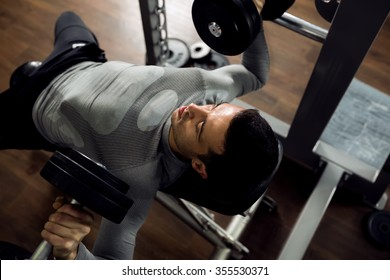 Man during bench press exercise at gym club