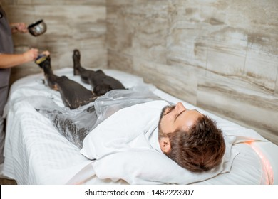 Man during a mud wrapping with special black mud, lying in the spa salon. Concept of a Detox mud body wraps