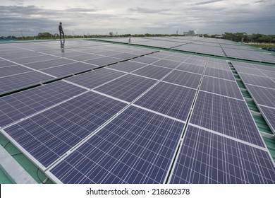 Man during survey of alternative energy photovoltaic solar panels on roof