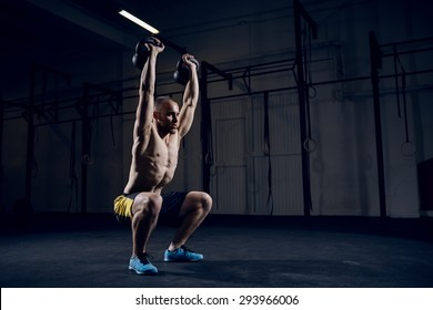 Man during workout gym. Squat with kettlebells over head