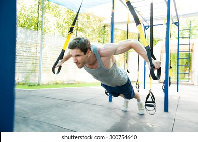 Man during workout with suspension straps on the street. Trx