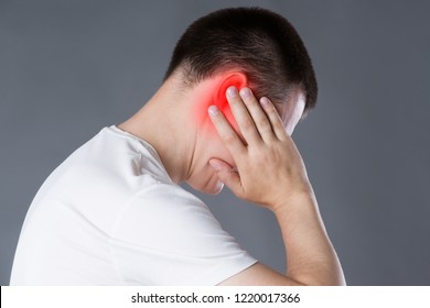 Man with earache, ear pain on gray background with red spot