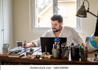 Man with earphones having conference call online sitting at home office with laptop. Working from home during quarantine and self isolation period at pandemic. Manager at online meeting