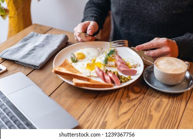 The man eat. Knife and fork in hand. The concept of eating at work. Laptop and Breakfast on the table.. American style breakfast with fried eggs, sausage, green peas and toast.