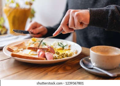 The man eat. Knife and fork in hand. Breakfast on the table.. American style breakfast with fried eggs, sausage, green peas and toast. The concept of a healthy morning.