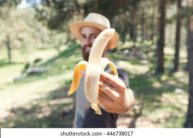 Man eating a banana in nature