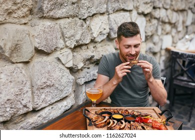 Man Eating Barbecue Meat With Beer. Handsome Man Having Dinner in Grill Restaurant. High Resolution