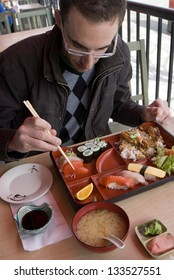 Man eating bento box sushi for lunch with chopsticks