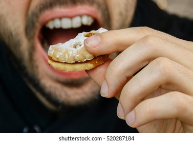 A man is eating a biscuit