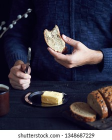 Man eating bread with butter on dark background