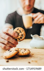 A man eating breakfast of cookies and cocoa with milk - homemade oatmeal cookies with chocolate chips - English breakfast close-up