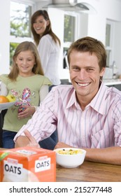 Man eating breakfast at table, smiling, portrait, family in background