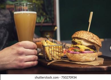 Man eating burgers at table at cafe