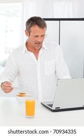 Man eating cereal while he is working on his laptop