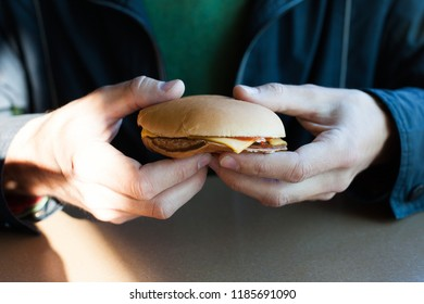 The man is eating a cheeseburger