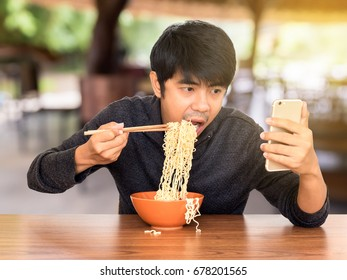 Man eating chinese noodle monstrously whilst looking and using smartphone. Concept of smartphone addiction, phubbing or social network issues