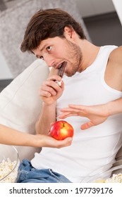 A man eating a chocolate refusing to take an apple