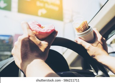 Man eating donuts and potato chip while driving car - multitasking unsafe driving concept